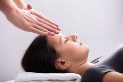 Tratamiento de Giving Reiki Healing del terapeuta a la mujer foto de archivo