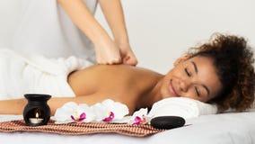 Tratamiento de la belleza Masajista que hace masaje trasero a la mujer relajada imagen de archivo libre de regalías