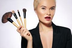 Tratamiento de la belleza Muchacha con los cepillos del maquillaje La moda compensa a la mujer atractiva makeover Artista de maqu imagen de archivo libre de regalías