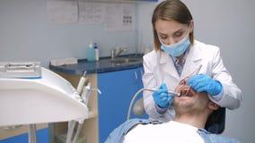 Tratamiento de la caries del dentista que conduce de sexo femenino almacen de metraje de vídeo