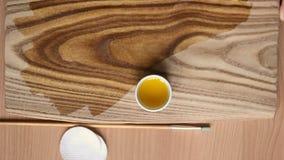 Tratamiento de la madera con la impregnación para la protección La mano femenina aplica el aceite de linaza en el tablero con una almacen de video