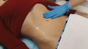 Tratamiento del cuerpo de la mujer en el centro médico del balneario aplicación de la crema hidratante en el estómago metrajes