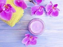 Tratamiento hermoso de la orquídea de la flor de la primavera cosmética poner crema de la despedregadora en fondo de madera imágenes de archivo libres de regalías