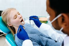 Tratamiento masculino asiático confiado joven de Medical del dentista a un paciente femenino en la clínica Concepto dental de la  fotografía de archivo libre de regalías