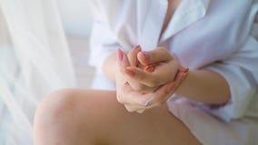 Tratamiento poner crema cosmético de aplicación modelo hermoso en su mano en fondo del dormitorio almacen de video