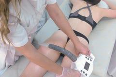 Tratamiento que contornea del cuerpo de la cavitación del ultrasonido Mujer que consigue las anti-celulitis y la terapia anti-gor imagen de archivo