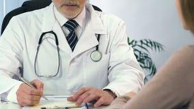 Tratamiento que prescribe del terapeuta profesional al paciente femenino en el hospital almacen de metraje de vídeo