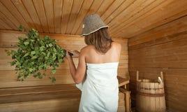 Tratan con vapor a la muchacha en la sauna Fotografía de archivo libre de regalías