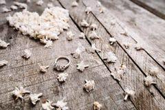Trate las flores blancas de la forma con suavidad del corazón con el anillo en la tabla de madera Fotos de archivo libres de regalías