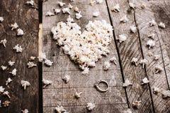 Trate las flores blancas de la forma con suavidad del corazón con el anillo en la tabla de madera Imagen de archivo libre de regalías