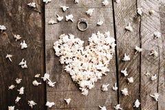 Trate las flores blancas de la forma con suavidad del corazón con el anillo en la tabla de madera Fotografía de archivo