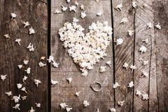 Trate las flores blancas de la forma con suavidad del corazón con el anillo en la tabla de madera Imagen de archivo