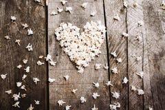Trate las flores blancas de la forma con suavidad del corazón en la tabla de madera Fotografía de archivo libre de regalías