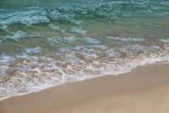 Trate las ondas con suavidad en la arena foto de archivo