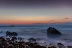 Trate las ondas con suavidad en la roca Imagenes de archivo