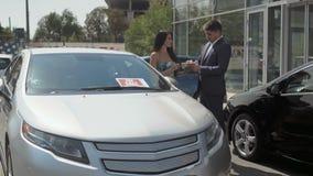 Trato acertado del automóvil de compra en la sala de exposición del coche al aire libre metrajes