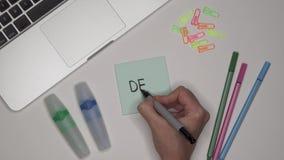TRATO de la escritura de la mujer en la libreta adhesiva Ordenador portátil y efectos de escritorio en la tabla almacen de metraje de vídeo