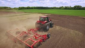 Trator agrícola com o reboque que ara no campo de cultivo Maquinaria de cultivo video estoque