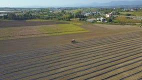 Trator agrícola em um campo marrom O zangão voa em torno de um trator que trabalha no campo no campo vídeos de arquivo