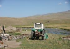 Trator agrícola no campo em Armênia com um rio pequeno Foto de Stock