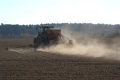 Trator agrícola que puxa um plantador atrás dele, sobre um campo e jogando acima lotes da poeira foto de stock royalty free