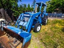 Trator azul velho com Front Scoop & o Backhoe Imagens de Stock Royalty Free