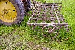 Trator com maquinaria velha do ancinho da agricultura na exploração agrícola Fotografia de Stock Royalty Free