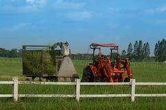 Trator com o cortador de grama da máquina de sega na exploração agrícola Fotografia de Stock