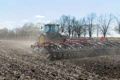 Trator com o plantador arrastado no campo imagem de stock