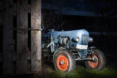 Trator de cultivo azul do oldtimer que está ao lado de um w Foto de Stock