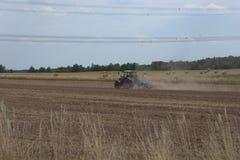 Trator de cultivo horroroso um campo seco, após uma colheita do verão, e o jogo acima de muita poeira da terra seca imagem de stock royalty free