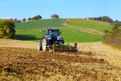 Trator de exploração agrícola no funcionamento do campo Foto de Stock