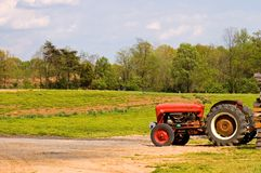 Trator de exploração agrícola vermelho perto do campo Fotos de Stock Royalty Free