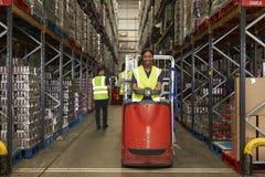 Trator do reboque do funcionamento da mulher em um armazém de distribuição ocupado fotografia de stock royalty free