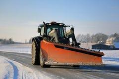 Trator e arado de neve na estrada Fotos de Stock Royalty Free