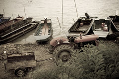 Trator e barcos velhos pelo rio Fotos de Stock Royalty Free