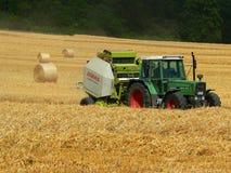 Trator e campo com trigo colhido em uns pacotes Fotografia de Stock