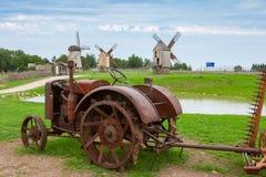 Trator e moinhos de vento velhos. Estónia foto de stock royalty free