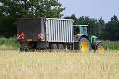 Trator em um campo durante a colheita Imagens de Stock Royalty Free