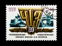 Trator, emblema e construção da fábrica, 50th aniversário Chelya foto de stock royalty free