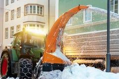 Trator grande com as correntes na neve de sopro da roda da rua da cidade no corpo do caminhão basculante Ruas de limpeza e remoçã imagem de stock royalty free