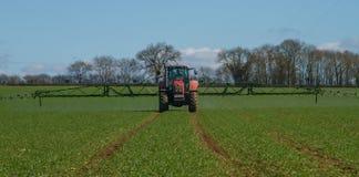 Trator moderno vermelho que puxa um pulverizador da colheita Foto de Stock Royalty Free