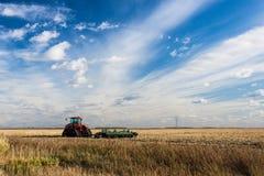 Trator no campo com o céu listrado azul Foto de Stock
