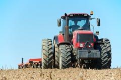 Trator Ploughing no trabalho do cultivo do campo Fotografia de Stock