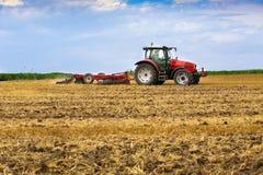 Trator que cultiva o campo de restolho do trigo, resíduo da colheita Fotografia de Stock Royalty Free