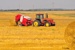 Trator que faz pacotes de feno no campo agrícola Imagem de Stock Royalty Free