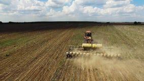 Trator que prepara a terra para semear dezesseis fileiras aéreas, conceito do cultivo, sementeira, arando o campo, o trator e o a filme