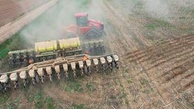 Trator que prepara a terra para semear dezesseis fileiras aéreas, conceito do cultivo, sementeira, arando o campo, o trator e o a video estoque