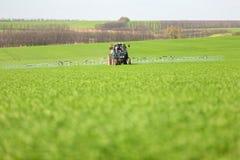 Trator que pulveriza um campo verde em uma exploração agrícola fotografia de stock royalty free