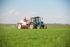Trator que pulveriza um campo verde em uma exploração agrícola foto de stock royalty free